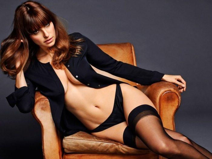 Lake Bell sitting on orange chair with no bra and high thighs on