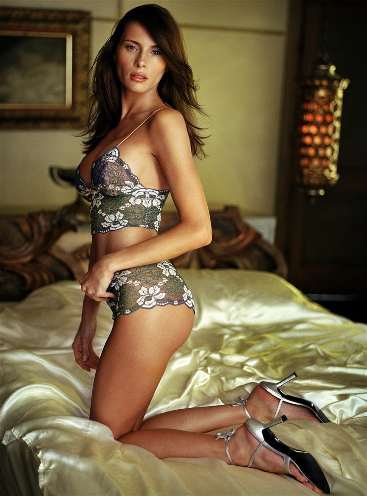 Melania Trump in lingerie kneeling on a bed with satin sheets
