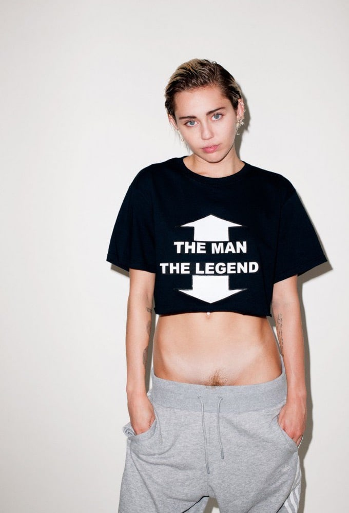 Miley Cyrus wearing a black crop top and sweat pants