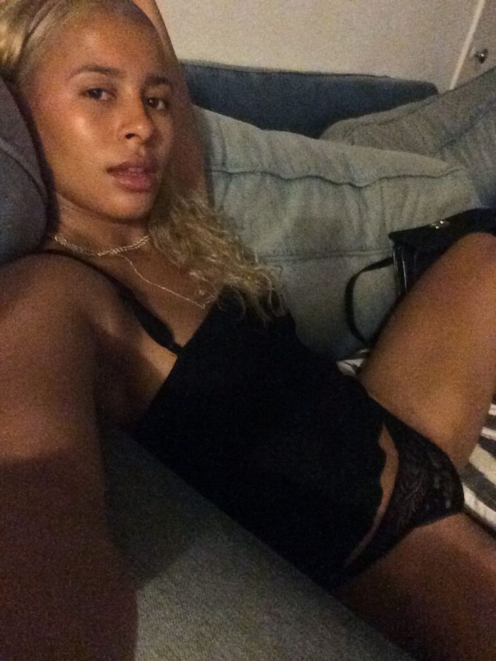 Sami Miro wearing a black top and underwear sitting on couch