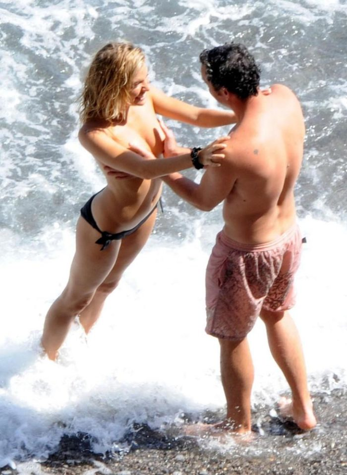 Sienna Miller at the beach topless standing in the ocean