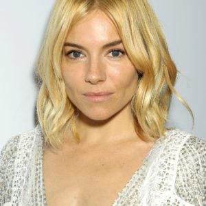 Sienna Miller in a low cut white dress exposing cleavage