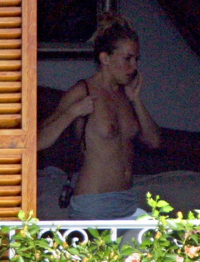 Sienna Miller on the phone with a purse on her arm on a balcony