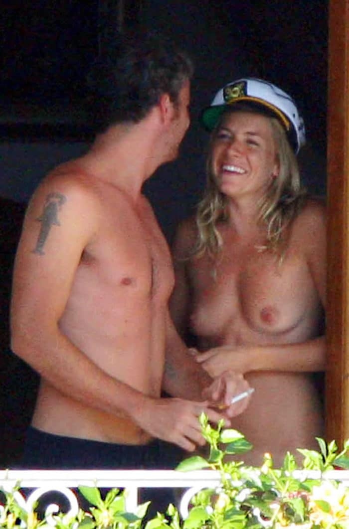 Sienna Miller smiling with a captain hat on in the doorway of her balcony