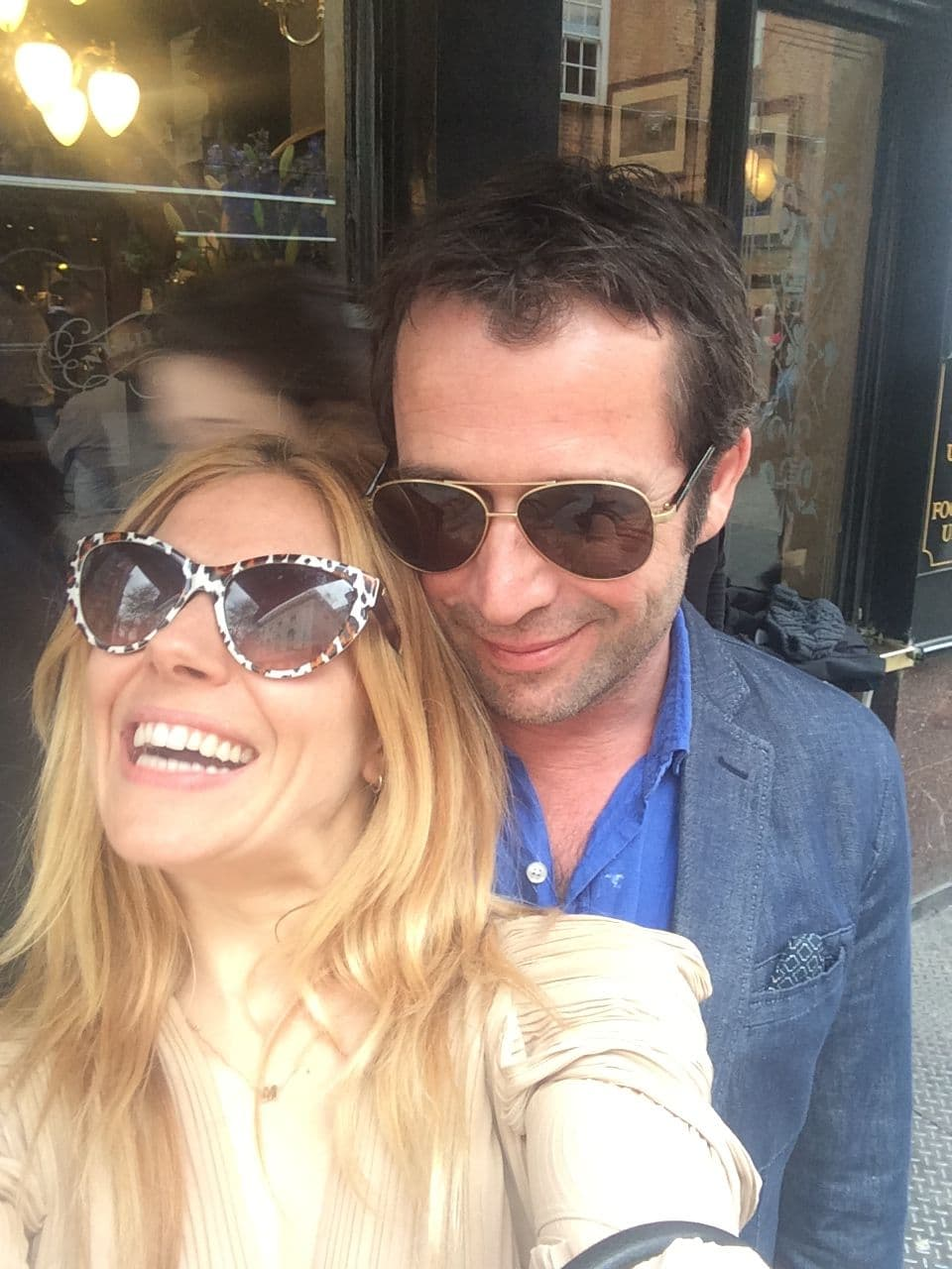 Sienna Miller taking a selfie with man as she laughs