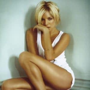 Sienna Miller tan in a white outfit sitting down with her had in her face