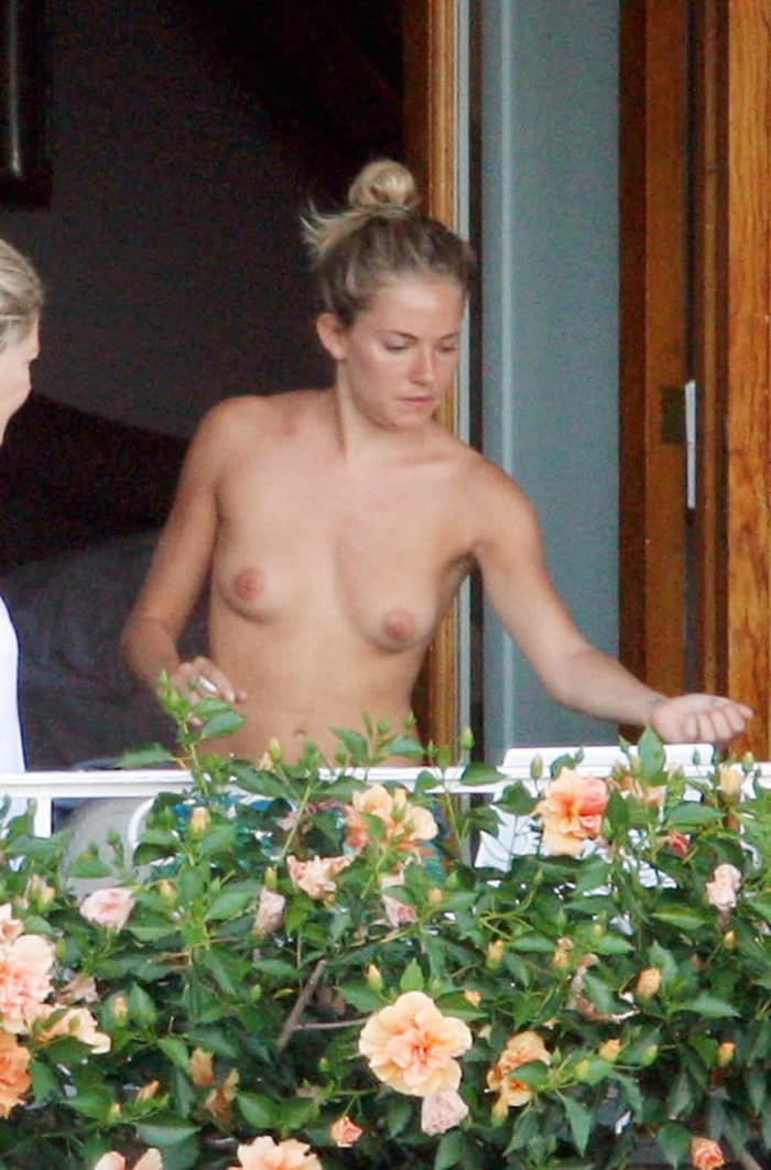 Sienna Miller unclothed on a balcony with her hair in a bun