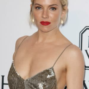 Sienna Miller wearing a gold dress showing cleavage and red lips