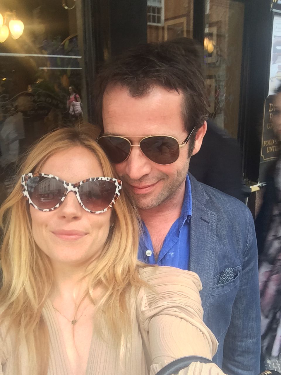 Sienna Miller wearing sunglass taking a selfie with man