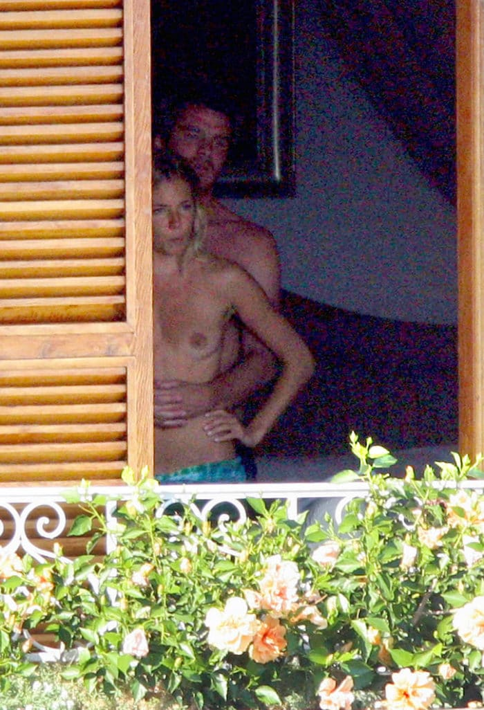 Sienna Miller with boyfriend topless on a balcony in the doorway