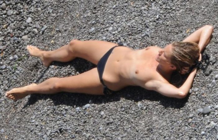 Sienna laying down with her hands behind her head on the sand without a bikini top on
