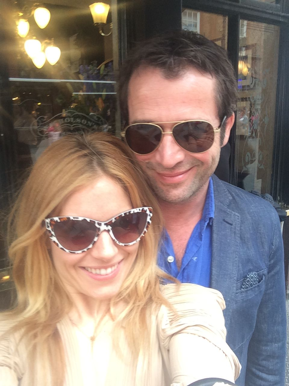 Sienne Miller and man take a selfie in sunglasses