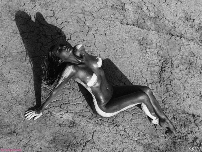 Black and white photo of Kim Kardashian naked in the desert