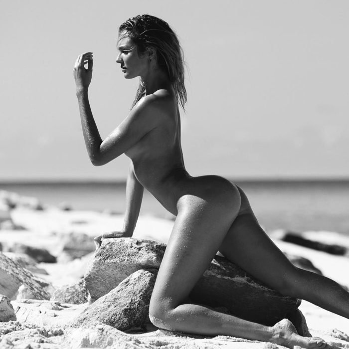 Black and white pic of Candice Swanepoel's naked butt on a rock