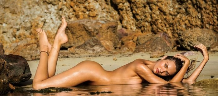 Candice Swanepoel laying down naked on the ground with feet in the air