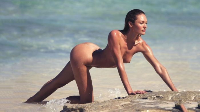 Candice Swanepoel on all fours in the sand on the beach
