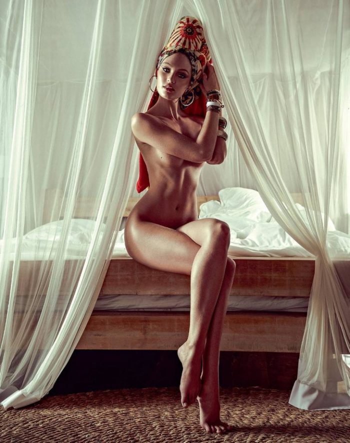 Candice Swanepoel sitting on a bed with legs crossed totally bare