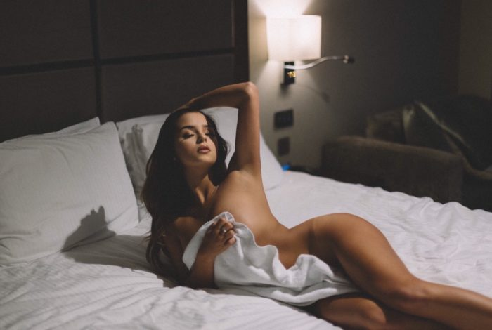 Demi Rose naked in bed covering herself with a towel