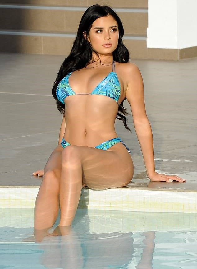 Demi Rose sitting pool side in Ibiza