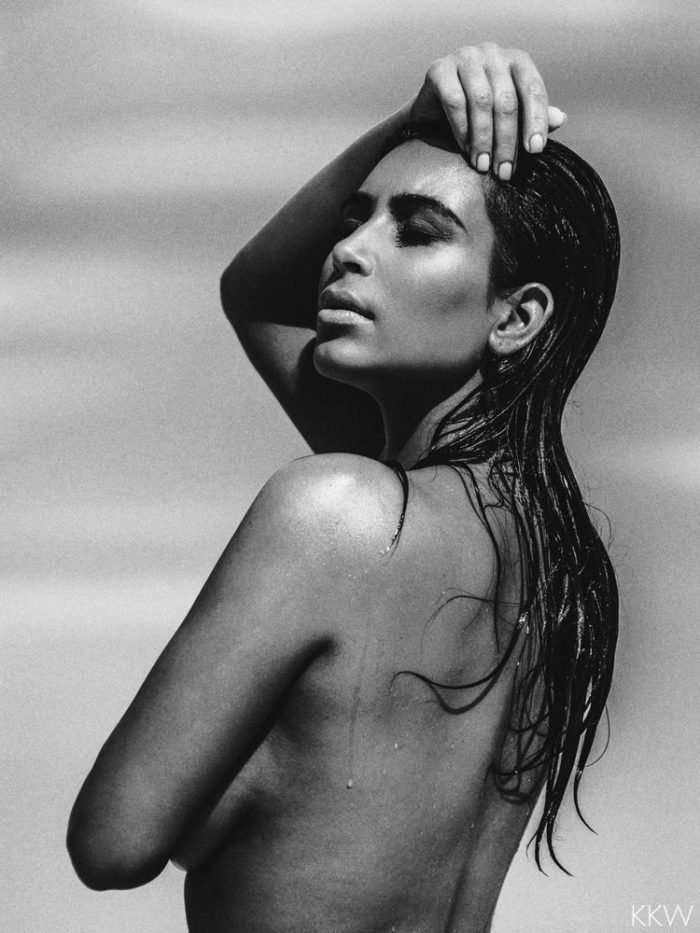 Kim Kardashian black and white photo of her modeling topless in the desert