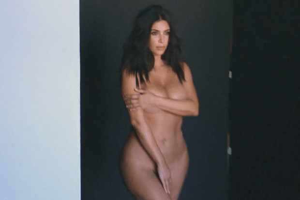 Kim Kardashian covering her naked bod with her arm and hand