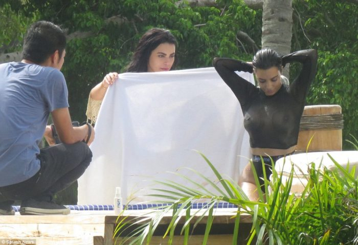 Kim Kardashian in see through black top sitting down