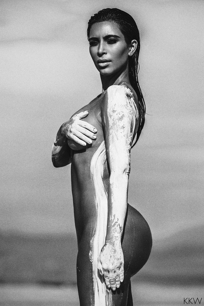 Kim Kardashian in the desert grabbing her boob in black and white pic