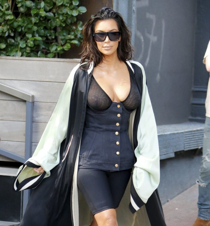 Kim Kardashian wearing sunglasses and see through top