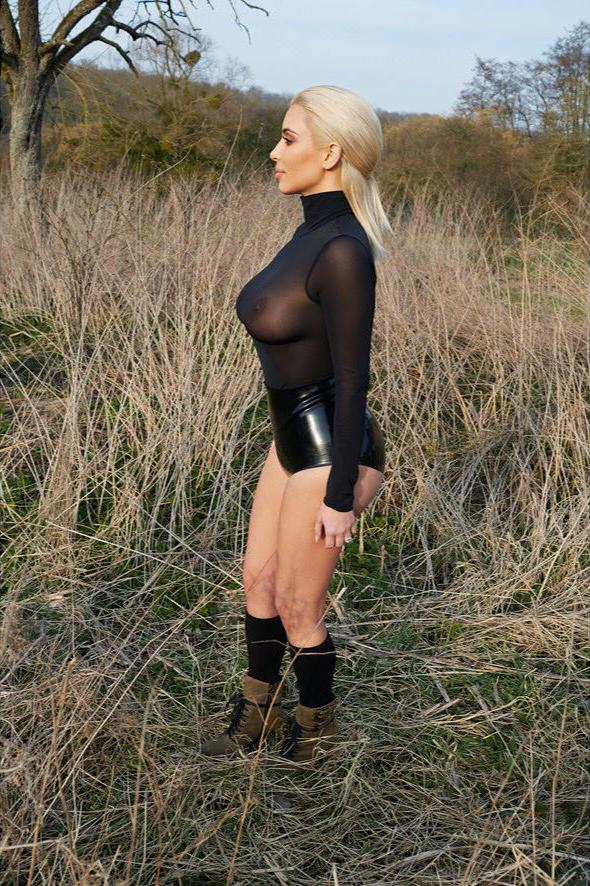 Kim Kardashian with blonde hair in a see through top modeling side view