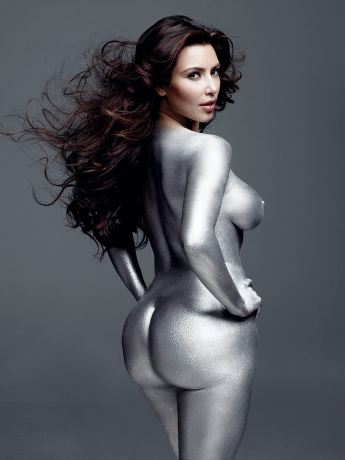 Kim Kardashian with silver paint all over her body looking back at the camera