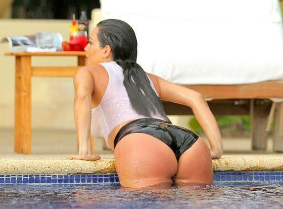 Kim getting out of the pool in a black bikini bottom